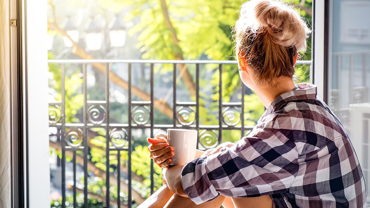 Vor einem offenen Fenster sitzend Kaffee trinken