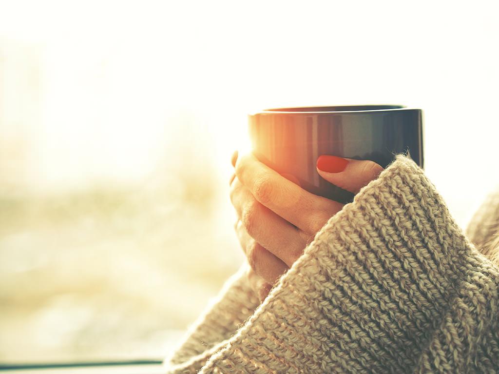 Hände halten eine heiße Tasse Tee in der Morgensonne